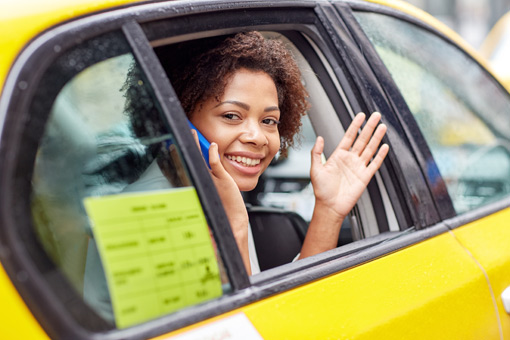 Woman waving hand from taxi